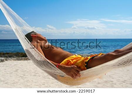 Goodlooking man, asleep in a hammock on a tropical beach. - stock photo