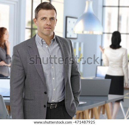 Goodlooking middle aged caucasian man in jacket standing at office.