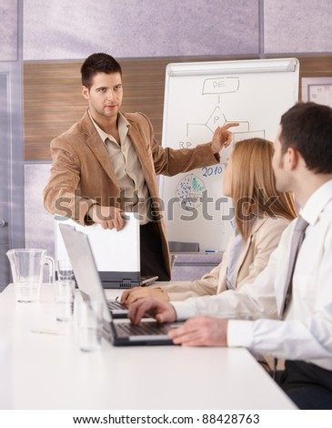 Goodlooking young businessman presenting over whiteboard to colleagues.? - stock photo