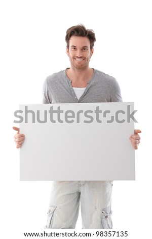Goodlooking young man holding a blank sheet, smiling.