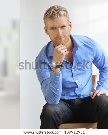 Goodlooking young man in modern office setting - stock photo
