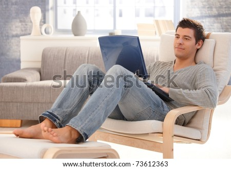 Goodlooking young man relaxing at home in armchair, sitting in living room with laptop computer, smiling.? - stock photo