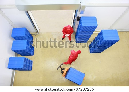 goods delivery in storehouse - overhead view of two workers working in small warehouse - stock photo