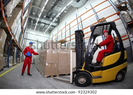 goods delivery in storehouse, two workers  reloading pallets  with  forklift truck - stock photo