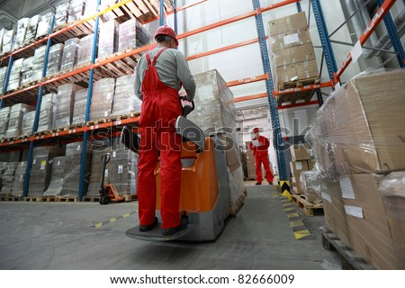 Goods delivery - two workers working in storehouse with forklift loader - stock photo