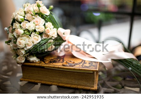 Goods for wedding: Bouquet and two Rings, Book. This photo is perfect for magazines, shops dealing with wedding dresses, ceremonies, bride, groom, marriage, jewelry. Can be used for wedding poster. - stock photo