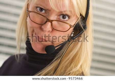 Goofy businesswoman makes a face while she talks on her phone headset. - stock photo