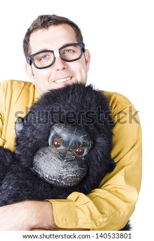 Goofy, smiling man in yellow shirt holding the head of a gorilla costume - stock photo
