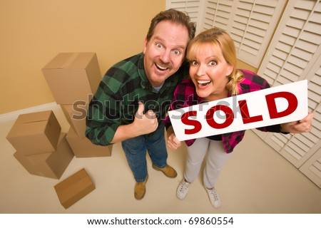 Goofy Thumbs Up Couple Holding Sold Sign in Room with Packed Cardboard Boxes.