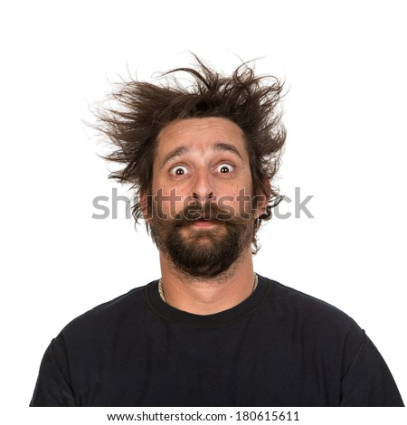Goofy young man, with full beard and moustache and wild hair, pull a comical face to the camera Studio portrait over white Space for your text - stock photo