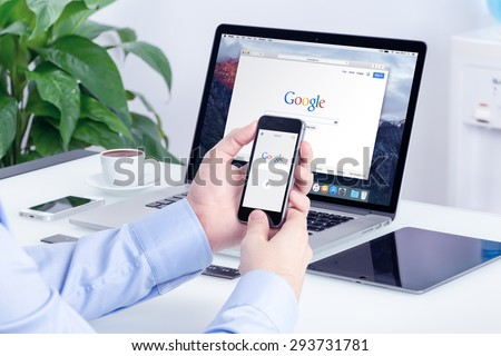 Google search on Apple iPhone screen and Macbook Pro Retina display that is on office desk. Multi devices multitasking concept. All gadgets in full focus. Varna, Bulgaria - May 29, 2015. - stock photo