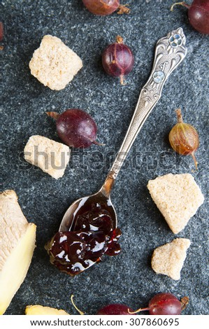 Gooseberry jam in the spoon with fresh Gooseberries, sugar and ginger, top view - stock photo