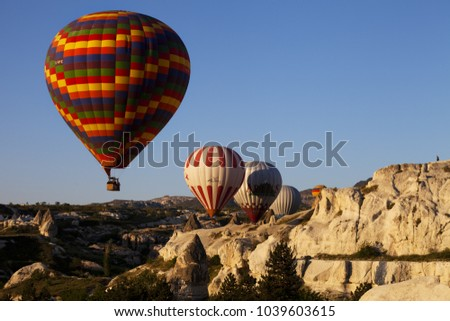 GOREM, CAPPADOCIA, TURKEY - MAY 07, 2013: Big multicolor hot air balloons in blue clear sky and fairy chimneys rock formations at sunny morning