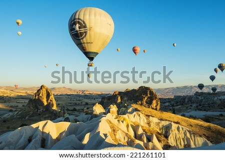 GOREME - OCTOBER 11: Colorful hot air balloons flying over ancient valleys in Cappadocia on October 11, 2013 in Goreme, Turkey. - stock photo