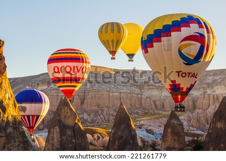 GOREME - OCTOBER 10 Colorful hot air balloons flying over rock landscape at Cappadocia on October 10, 2013 in Goreme, Turkey. - stock photo