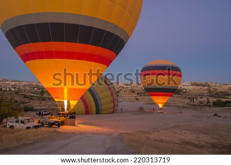 GOREME - OCTOBER 10: Colorful hot air balloons inflating before the flight at sunrise in Cappadocia on October 10, 2013 in Goreme, Turkey.  - stock photo