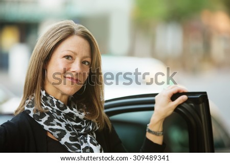 Gorgeous adult business woman standing at car door - stock photo