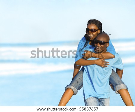 Gorgeous African American couple have fun at the seaside - stock photo