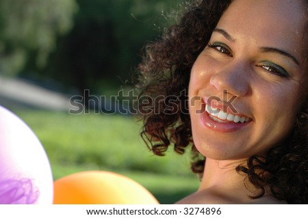 Gorgeous American girl of mixed heritage holding festive party balloons and laughing - stock photo