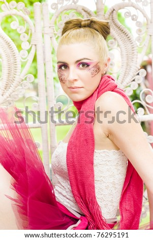 Gorgeous And Attractive Blonde Ballerina Dancer Woman Stares Directly At While Sitting In A Pink Leotard In A Dance Or Dancing Concept - stock photo
