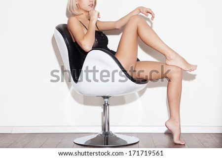 Gorgeous and bossy. Side view cropped image of gorgeous young blond hair woman in lingerie sitting in chair - stock photo