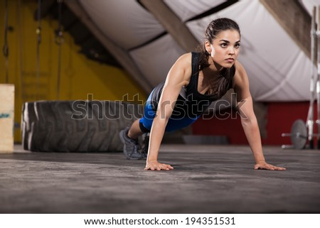 Gorgeous and strong brunette doing a set of push ups in a gym - stock photo