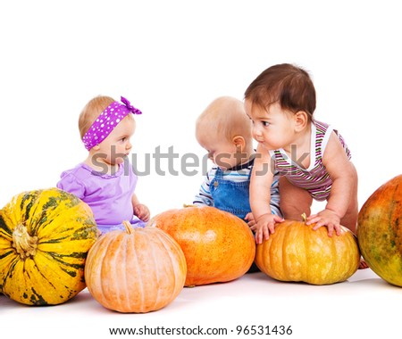 Gorgeous babies group sit among pumpkins