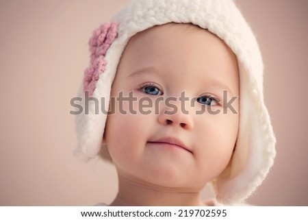 Gorgeous baby girl, looking into the camera with beautiful blue eyes. - stock photo