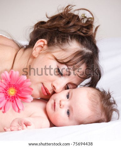 Gorgeous baby looking at the pink flower, mother lying beside - stock photo