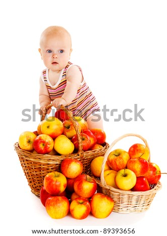Gorgeous baby standing beside baskets full of apples - stock photo