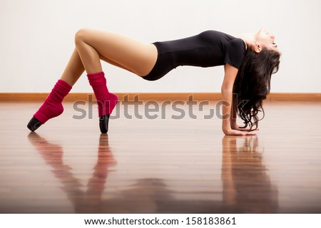 Gorgeous ballet dancer practicing some moves in the dance floor - stock photo