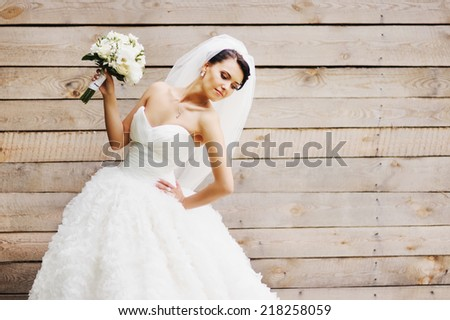 Gorgeous beautiful brunette  bride in white dress with bouquet on wood background.  - stock photo