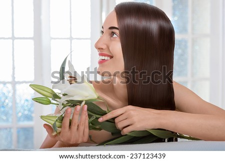 Gorgeous beautiful caucasian female model with perfect hair holding flower and lying on towel in spa salon with windows on background - stock photo