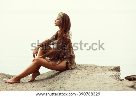 Gorgeous bikini woman sitting on beach with nice figure wearing silk turban and pareo cover up beachwear - weight loss, fashion, luxury concept. Copy-space. Retro, vintage style. Outdoor shot - stock photo