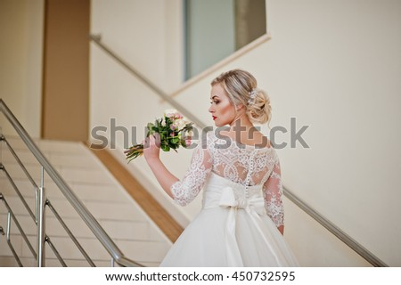 Gorgeous blonde bride posed at stairs indoor great wedding hall - stock photo