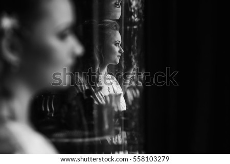 Gorgeous blonde bride posing near mirror, reflection of sexy woman in stylish robe sitting in front of fairytale mirror, morning wedding preparation, face closeup