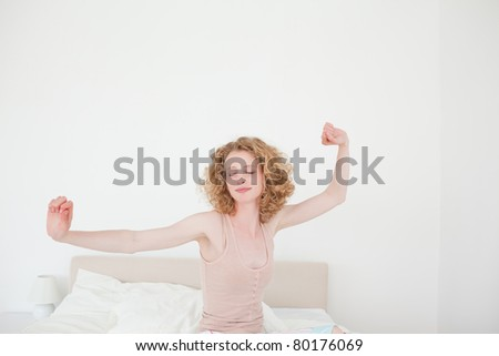 Gorgeous blonde female stretching in her bedroom in her apartment - stock photo