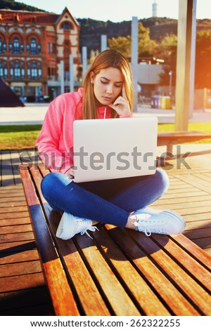 Gorgeous blonde hair female student focused and busy using laptop computer at campus, charming female teenager sitting on park bench with open laptop at spring sunny day, flare sun - stock photo