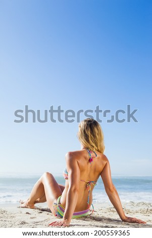 Gorgeous blonde in bikini lying on the beach on a sunny day - stock photo