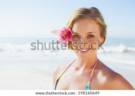 Gorgeous blonde in bikini smiling at camera on the beach on a sunny day - stock photo