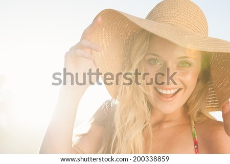 Gorgeous blonde in straw hat smiling at camera on beach on a sunny day - stock photo