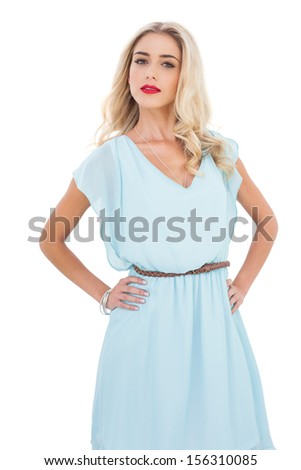 Gorgeous blonde model in blue dress posing hands on the hips on white background - stock photo