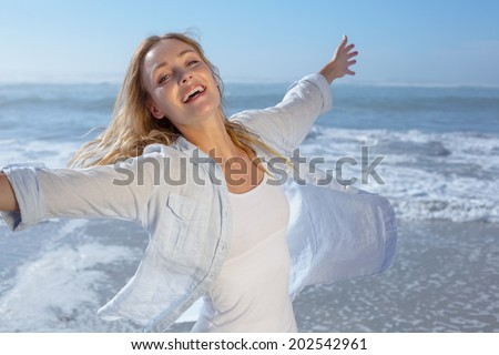 Gorgeous blonde spreading arms out at the beach on a sunny day - stock photo