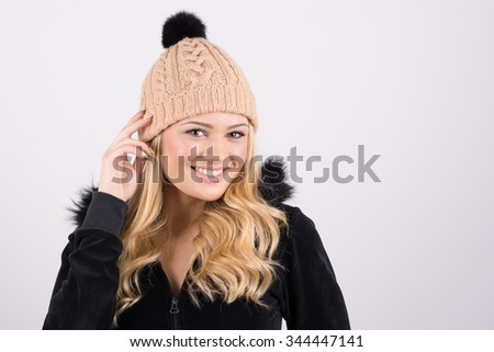 Gorgeous blonde teenage girl in black sweatshirt and knitted beige hat smiling and posing. Horizontal, copy space, mild retouch, studio shot. - stock photo