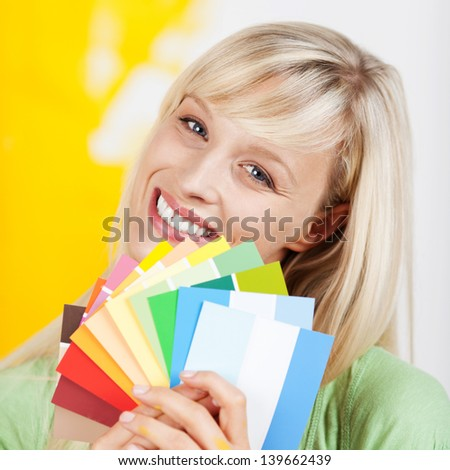 Gorgeous blonde woman holding up a selection of beautiful new paint colours on swatches when renovating and decorating her house - stock photo