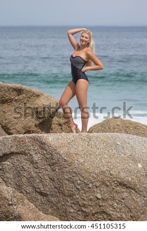 Gorgeous Blonde woman in a swimsuit posing for the camera with the beach in the background - stock photo