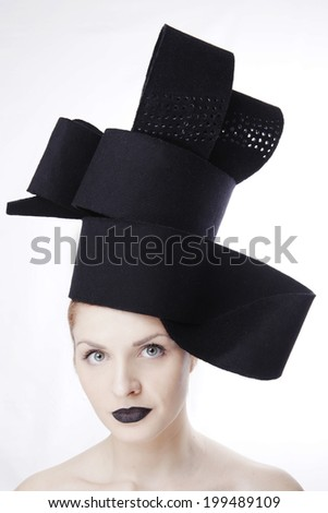 Gorgeous blonde woman model with blue eyes and black lipstick wearing big stylish designer black unique hat/ headpiece. Isolated on white background. Studio closeup - stock photo