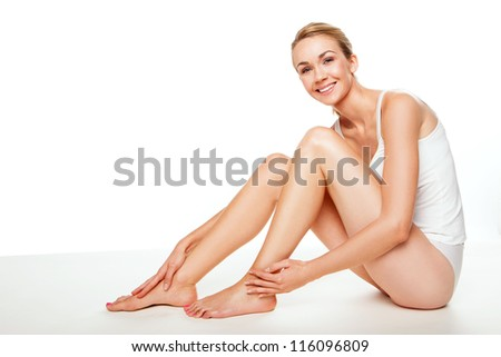 Gorgeous blonde woman with sexy bare long legs sitting on the floor in a vest and panties exuding health, happiness and vitality - stock photo