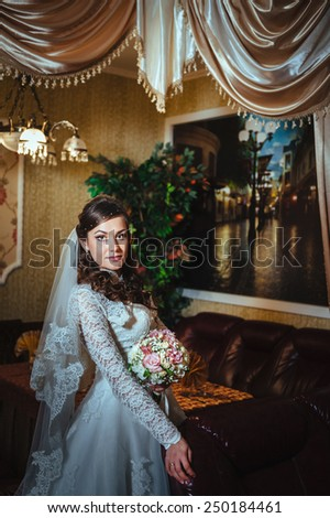 Gorgeous bride blonde in wedding dress in luxury interior posing at home and waiting for groom. Romantic rich beautiful brunette bride in a luxurious wedding dress in elegant expensive interior