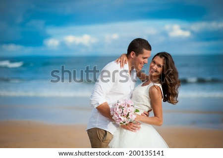 Gorgeous bride in a wedding dress and a handsome groom getting married at a beautiful beach - stock photo